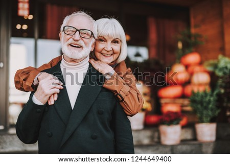 Waist up portrait of happy lady hugging husband from behind while he holding her hand. They looking at camera and smiling #1244649400