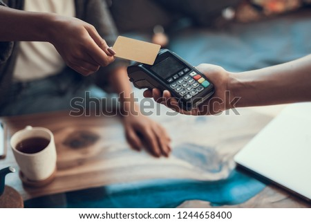 Hands of cafe visitor holding credit card and putting it to the card payment machine #1244658400