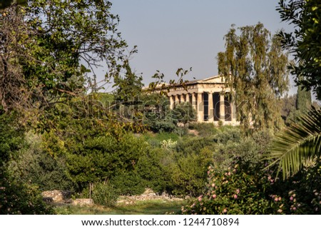 The Temple of Hephaestus with Doric columns rises in the distance, past trees, in the Ancient Agora of Athens, Greece. #1244710894