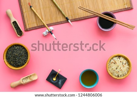 Chinese traditional symbols concept. Tea, rice, hieroglyph love, bamboo table mat, chopsticks, soy sause on pink background top view frame space for text #1244806006