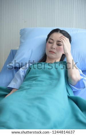The patient sleeps in a hospital bed. Waiting to see sick #1244814637