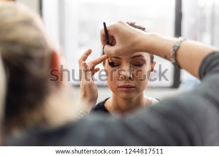 Makeup artist applying eyeshadow onto model #1244817511