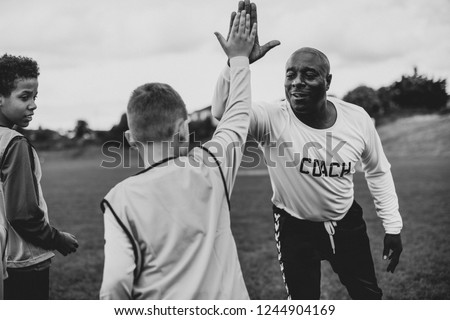 Football coach doing a high five with his student Royalty-Free Stock Photo #1244904169