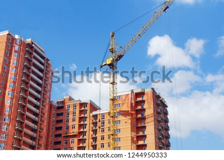 Construction site background. High-rise red brick building under construction. Crane near the building under construction. #1244950333