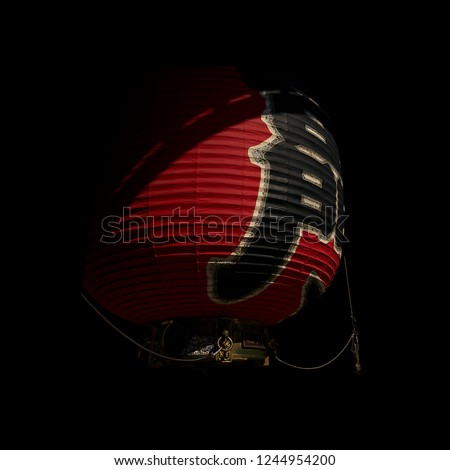 """Giant, red, paper lantern with the Japanese characters for """"Thunder Gate,"""" lit by afternoon sun with black background (Kaminarimon Gate at Sensoji Temple in Asakusa, Tokyo, Japan)."""