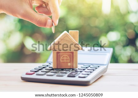 House is placed on the calculator. hand that is coin down the house. planning savings money of coins to buy a home concept for property, mortgage and real estate investment.to buy a house. #1245050809