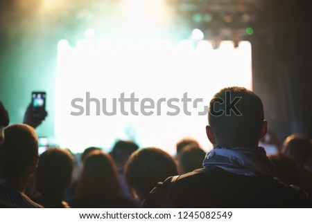 Concert crowd with arms raised, silhouettes of people with smartphones. #1245082549