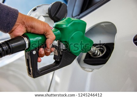 Man Handle pumping gasoline fuel nozzle to refuel. Vehicle fueling facility at petrol station. White car at gas station being filled with fuel. Transportation and ownership concept. #1245246412