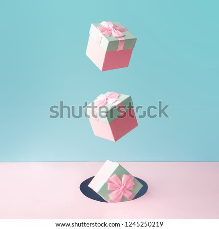 Pastel pink Christmas gift boxes on blue and pink backdrop. New Year present concept. Minimal composition. #1245250219