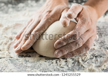 Male chef hands knead dough with flour on kitchen table side view #1245255529