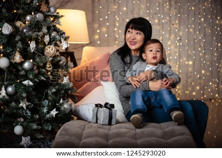 Little baby boy in a casual jacket and jeans sitting near christmas tree with his grandmother #1245293020