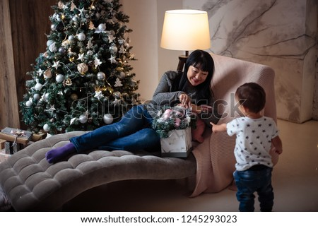Little baby boy in a casual jacket and jeans sitting near christmas tree with his grandmother #1245293023