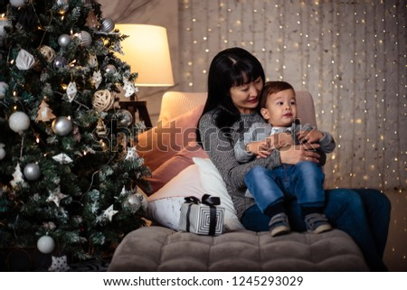Little baby boy in a casual jacket and jeans sitting near christmas tree with his grandmother #1245293029