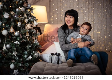 Little baby boy in a casual jacket and jeans sitting near christmas tree with his grandmother #1245293035