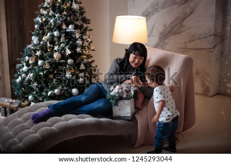 Little baby boy in a casual jacket and jeans sitting near christmas tree with his grandmother #1245293044