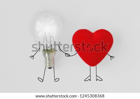 Light bulb and heart holding hands - Concept of brain and heart teamwork