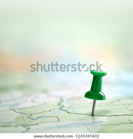 Pushpin showing the location of a destination point on a green map #1245341602