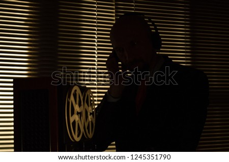 Special agent intelligence officer listens to conversations and records on a reel to reel tape recorder 4 #1245351790