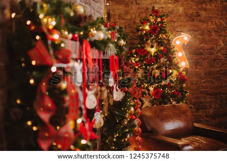 christmas background with bokeh cozy room interior tree decorated by lights gifts toys candles holiday concept #1245375748