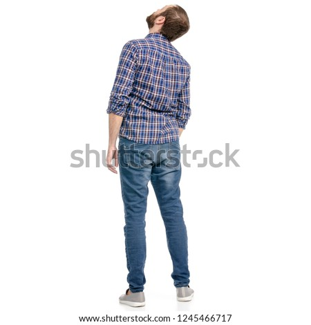 A man in jeans looking up on a white background isolation back view Royalty-Free Stock Photo #1245466717