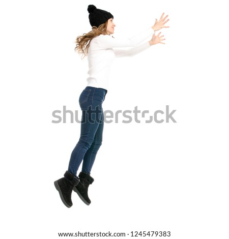 Beautiful woman in sweater jeans hat cold showing of positive emotions runs jumping on white background isolation back view #1245479383