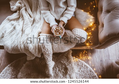 Cold autumn or winter weekend while drinking warm cocoa with marshmellows. Lazy day in knitted socks on the couch. Cosy scene, hygge concept, top veiw. #1245526144