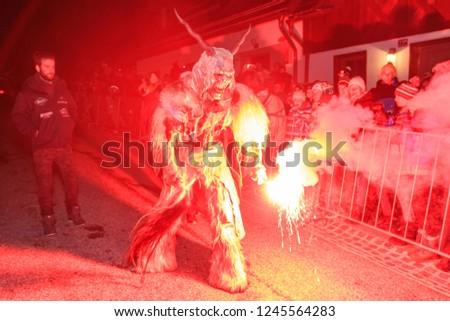 "PODKOREN, SLOVENIJA - NOVEMBER 30th 2018: Unidentified man wears Krampus (devil) mask at traditional procession  ""Parkelj gathering"" in Podkoren, Slovenia #1245564283"