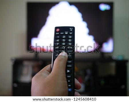 closeup of hand with the remote control television and presses the button. #1245608410