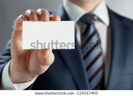 Man's hand showing business card - closeup shot on grey background