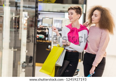 Young cheerful woman going along shopping centre with colourful paper bags showing something in the shop window to her blonde girlfriend, being fascinated by what she found. #1245927193