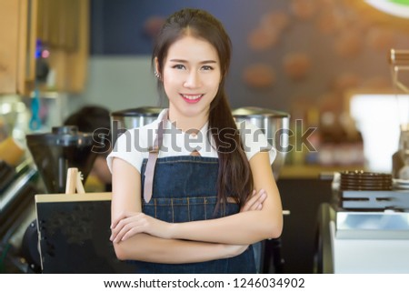 Young beautiful barista female in an apron preparing cup of coffee for customer in coffee shop. on demand #1246034902