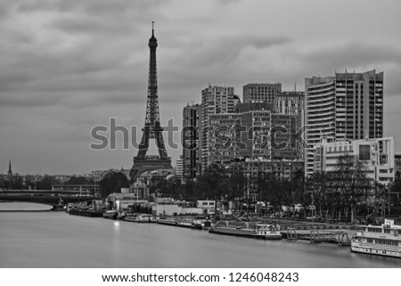 Black and white Eiffel Tower with beautiful dramatic clouds and surrounding apartment buildings. Seine river and a bridge is also part of the picture with boats floating in the margins of Seine river.