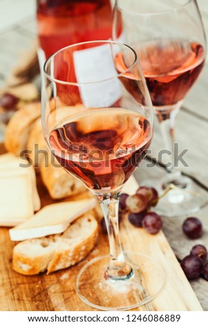 Two glasses of rose wine and board with fruits, bread and cheese on wooden table  #1246086889