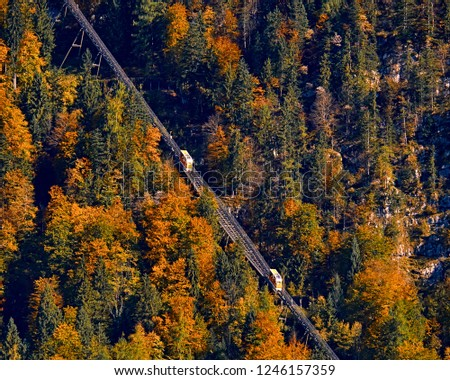 Beautiful aerial fall view of cable car ropeway funicular in austrian alps. Red cable railway car in the mountains by resort village Hallstatt, Salzkammergut, Austria, Alps. #1246157359