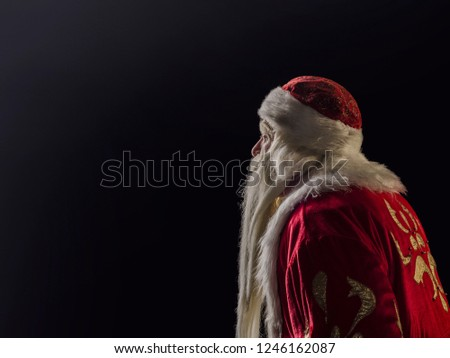 Santa Claus and Santa Claus on a black background. Santa Claus and Santa Claus majestic, looks away, in profile against a black background. #1246162087