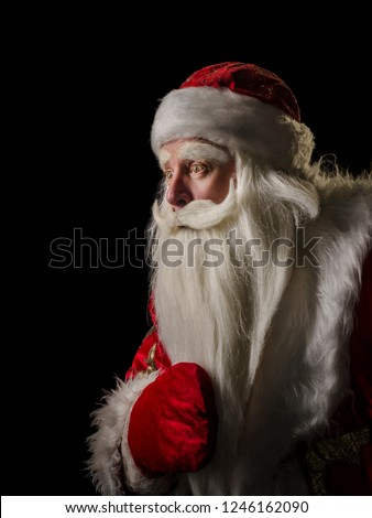 Santa Claus and Santa Claus on a black background. Santa Claus and Santa Claus majestic, looking amazed at the side, in profile against a black background. #1246162090