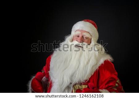 Santa Claus and Santa Claus on a black background. Santa Claus and Santa Claus majestic smiling and grinning and greeting against a black background. #1246162108