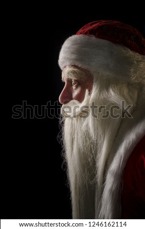 Santa Claus and Santa Claus on a black background. Santa Claus and Santa Claus majestic, looks away, in profile against a black background. #1246162114
