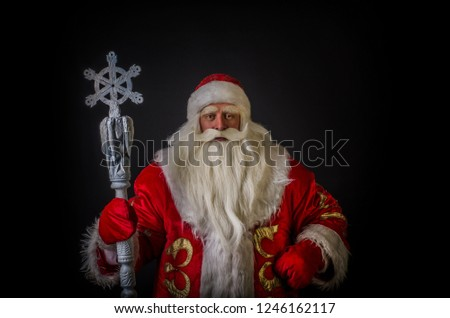 Santa Claus and Santa Claus on a black background. Santa Claus and Santa Claus are majestic and original with a staff on a black background. #1246162117