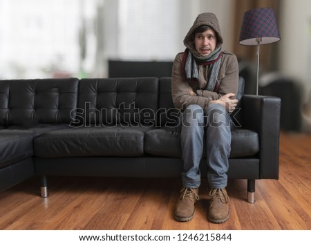 Young man sitting on couch is feeling cold at home. Royalty-Free Stock Photo #1246215844