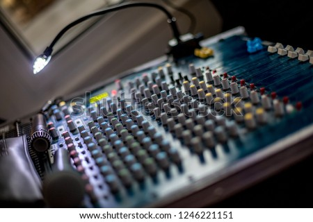 Selective focus or shallow depth of field night photo of audio mixer with small lamp switched on and microphone. Blurred background #1246221151