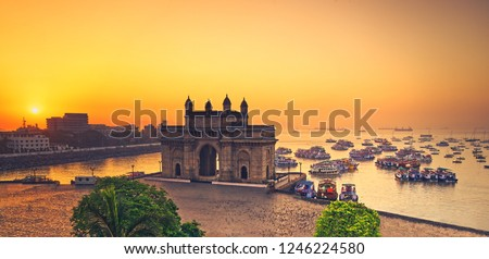 The gateway of India at sunrise with beautiful reflections in the sea. Boats in the water in a hot day. Royalty-Free Stock Photo #1246224580
