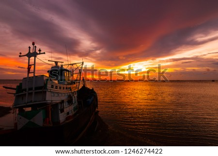 Fishing boat is on the sea water with sunset cloud and sky. #1246274422