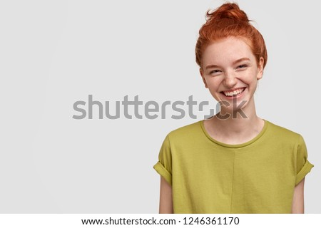 Isolated shot of pretty adult with foxy hair, broad smile, wears casual outfit, being entertained by friend during party, tilts head and looks with joy, dressed casually, models over white wall #1246361170