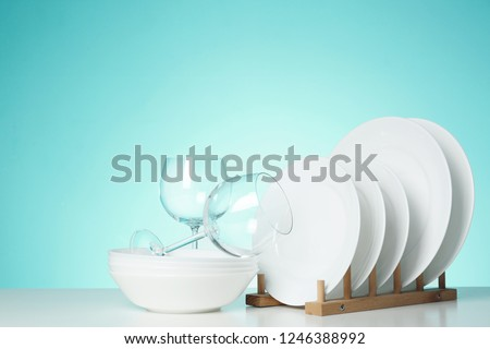 Set of clean dishes and glasses on table against color background #1246388992