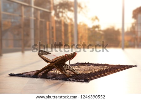 Rehal with open Quran and Muslim prayer beads on rug indoors. Space for text #1246390552