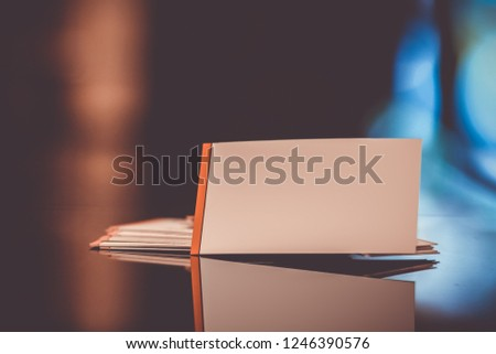 White Business Card Mockup label on a blurred black and brown background with reflection.