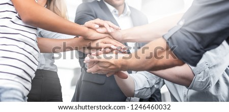 Close up view of young business people putting their hands together. Stack of hands. Unity and teamwork concept. #1246460032