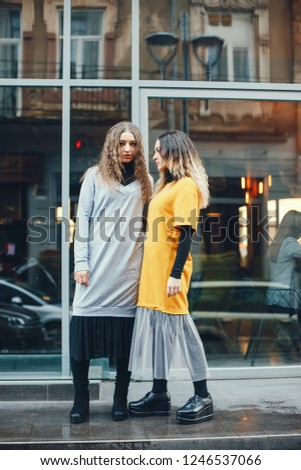 two beautiful and stylish girls in fashion clothes are walking in the spring city #1246537066