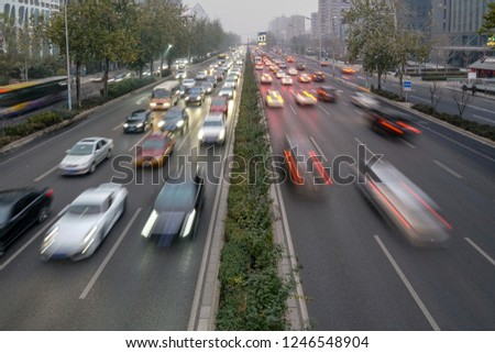 Speed Traffic, light trails on motorway highway at dusk. Starting night traffic in the city during polluted day. Beijing, China 2018/12/02 #1246548904